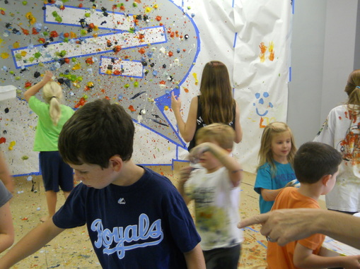 Splat Painting is a wild, messy, large-scale art project for a group. Great for kids birthday parties if you've got the space for it! Outside maybe? {ORANGE EASEL ART}